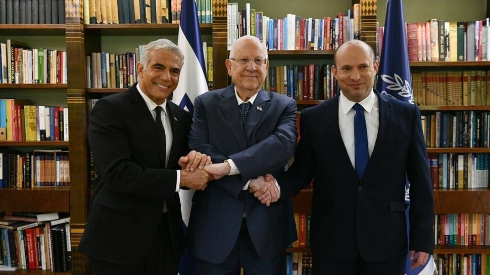JERUSALEM - JUNE 14: Israeli President Reuven Rivlin (C) shake hands with Prime Minister Naftali Bennett (R) and Alternate Israeli Prime Minister and Foreign Minister Yair Lapid (L) after the Knesset (Israelâs parliament) gave confidence on Sunday to the new coalition government, at the President's Residence in Jerusalem on June 14, 2021. (Photo by GPO/Anadolu Agency via Getty Images)