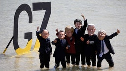 Extinction Rebellion protesters stand in front of a G7 sign wearing masks depicting from left to right, Yoshihide Suga, Japan's prime minister, Emmanuel Macron, France's president, Angela Merkel, Germany's chancellor, Justin Trudeau, Canada's prime minister, U.S. President Joe Biden, and Boris Johnson, U.K. prime minister, on the beach on the sidelines of the final day of the Group of Seven leaders summit, in St. Ives, U.K., on Sunday, June 13, 2021. The worlds richest governments are under mounting pressure to help poor countries fight climate change. Photographer: