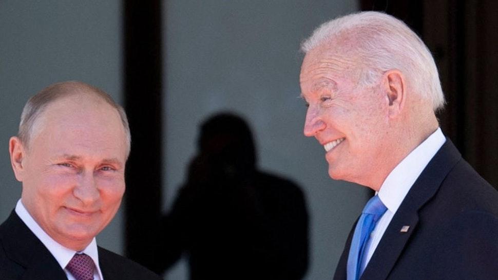 TOPSHOT - Russian President Vladimir Putin (L) shakes hands with US President Joe Biden prior to the US-Russia summit at the Villa La Grange, in Geneva on June 16, 2021. (Photo by Brendan Smialowski / AFP) (Photo by