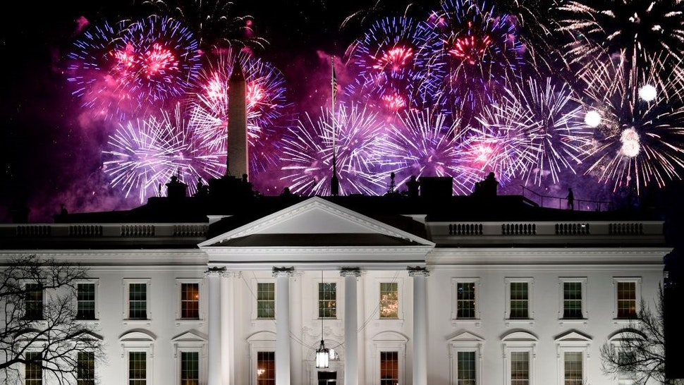 TOPSHOT - Fireworks are seen above the White House, with US Secret Service members watching from its roof, at the end of the Inauguration day for US President Joe Biden in Washington, DC, on January 20, 2021. (Photo by Patrick T. FALLON / AFP) (Photo by