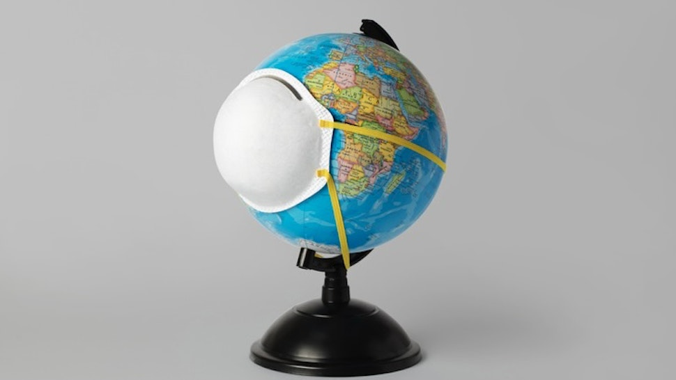 Pandemic - stock photo World Globe whit a face mask Roc Canals via Getty Images