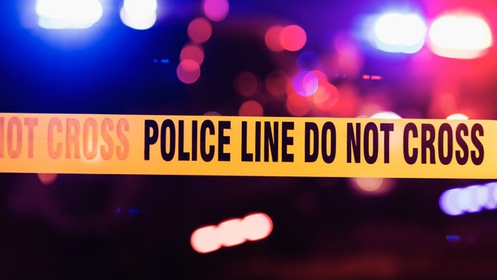 Accident or crime scene cordon tape - stock photo Accident or crime scene cordon tape, police line do not cross. It is nighttime, emergency lights of police cars flashing blue, red and white in the background kali9 via Getty Images