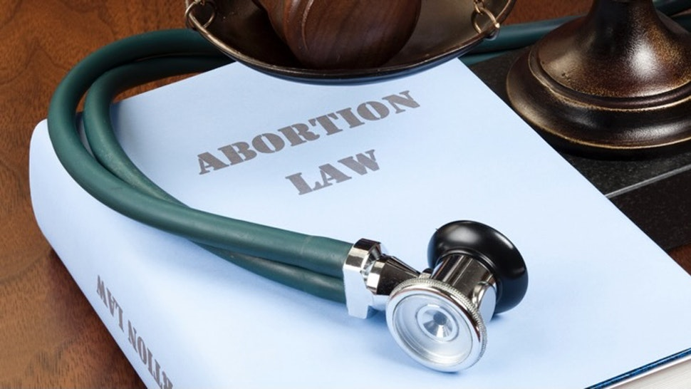 """Abortion law - stock photo """"Concept shot. Gavel, stethoscope and scale of justice next to Abortion Law book."""" ericsphotography via Getty Images"""