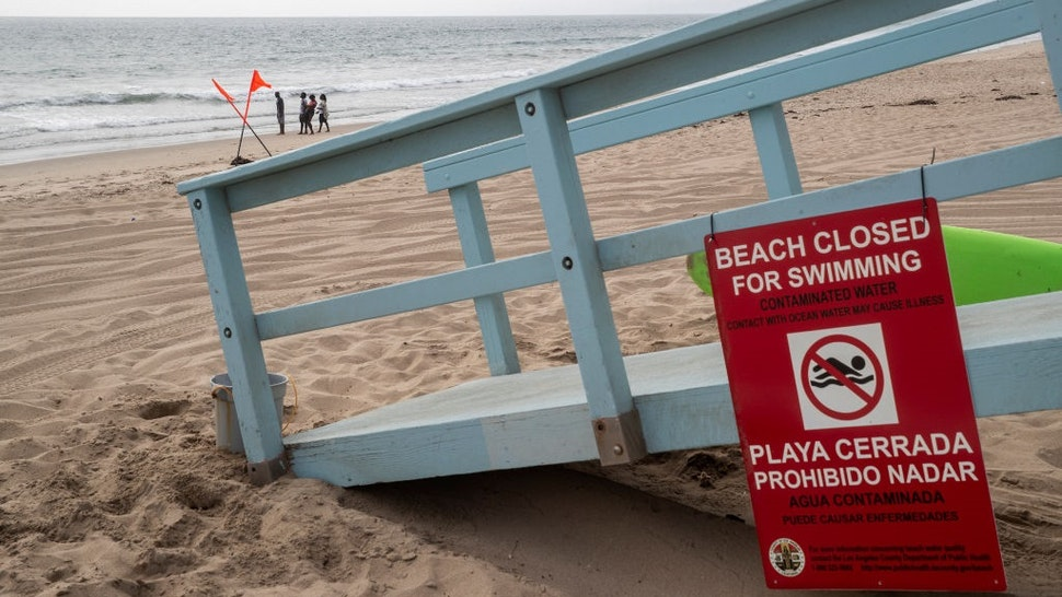 PLAYA DEL REY , CA - JULY 12, 2021: A sign at a lifeguard station at Dockweiler State Beach in Playa del Rey warns the public that the beach is closed to swimming as a result of 17 million gallons of untreated sewage, caused by a power outage at the nearby Hyperion Treatment Plant in Playa Del Rey, spilling into the ocean.