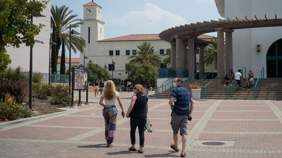 Students and parents walk on campus during move-in day at San Diego State University in San Diego, California, U.S., on Friday, Aug. 21, 2020.