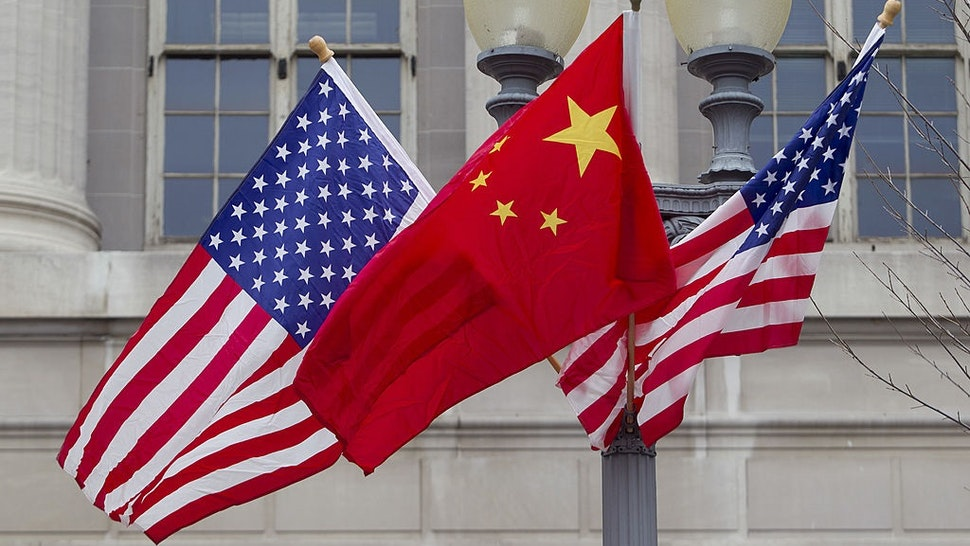 Flags of the U.S. and China fly along Pennsylvania Avenue in Washington, D.C., U.S., on Monday, Jan. 17, 2011.