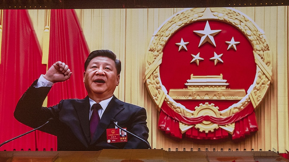 BEIJING, CHINA - JUNE 28: Chinese President and Chairman of the Communist Party Xi Jinping appears on a large screen as performers dance during a mass gala marking the 100th anniversary of the Communist Party on June 28, 2021 at the Olympic Bird's Nest stadium in Beijing, China. China will officially mark the100th anniversary of the founding of the Communist Party on July 1st.