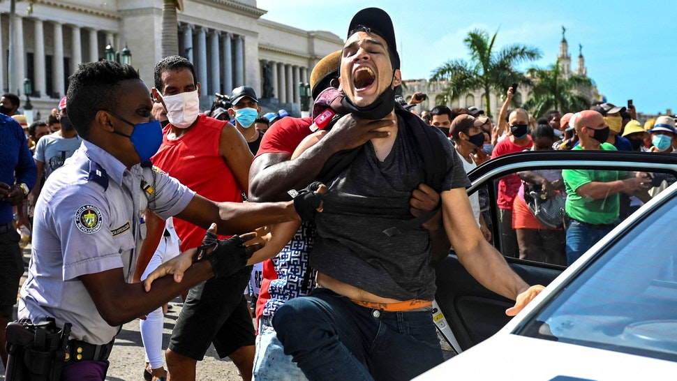 """A man is arrested during a demonstration against the government of Cuban President Miguel Diaz-Canel in Havana, on July 11, 2021. - Thousands of Cubans took part in rare protests Sunday against the communist government, marching through a town chanting """"Down with the dictatorship"""" and """"We want liberty."""""""