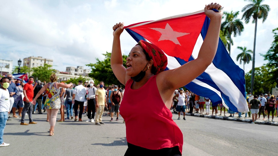 """A pro-government woman is seen during a demonstration against the government of Cuban President Miguel Diaz-Canel in Havana, on July 11, 2021. - Thousands of Cubans took part in rare protests Sunday against the communist government, marching through a town chanting """"Down with the dictatorship"""" and """"We want liberty."""""""