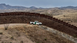 A Border Patrol officer sits inside his car as he guards the US/Mexico border fence, in Nogales, Arizona, on February 9, 2019.