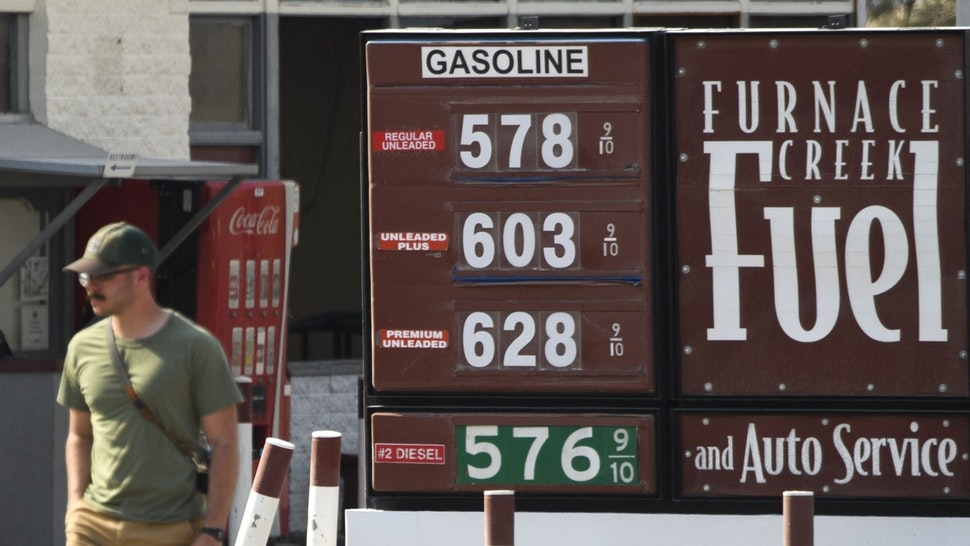 """A pedestrian walks past gas station fuel prices above $5 and $6 per gallon at Death Valley National Park in June 17, 2021 in Furnace Creek, California. - Much of the western United States is braced for record heat waves this week, with approximately 50 million Americans placed on alert Tuesday for """"excessive"""" temperatures, which could approach 120 degrees Fahrenheit (50 degrees Celsius) in some areas. The National Park Service warns of extreme summer heat, urging tourists to carry extra water and """"travel prepared to survive"""" in the hottest, lowest, and driest national park featuring steady drought and extreme climates."""