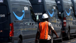 Amazon vans line up at a distribution center to pick up packages for delivery on Amazon Prime Day, July 16, 2019, in Orlando, Florida.