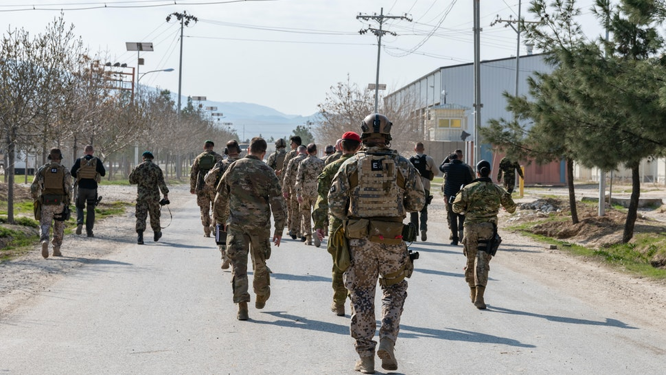 Rear View Of Army Soldiers Walking On Road In City - stock photo