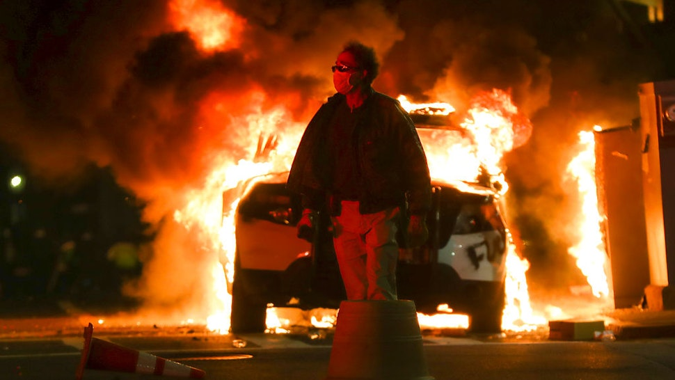 BOSTON, MA - JUNE 1: An unidentified man walks past a burning Boston Police car on Tremont Street in Boston on May 31, 2020 after a peaceful march from Dudley Square to the State House protesting the murder of George Lloyd by in Minneapolis by a police officer. (Photo by Matthew J. Lee/The Boston Globe via Getty Images)