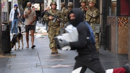 TOPSHOT - A suspected looter carrying boxes of shoes run past National Guard soldiers in Hollywood, California, June 1, 2020, after a demonstration over the death of George Floyd. - Major US cities -- convulsed by protests, clashes with police and looting since the death in Minneapolis police custody of George Floyd a week ago -- braced Monday for another night of unrest. More than 40 cities have imposed curfews after consecutive nights of tension that included looting and the trashing of parked cars. (Photo by Robyn Beck / AFP) (Photo by ROBYN BECK/AFP via Getty Images)