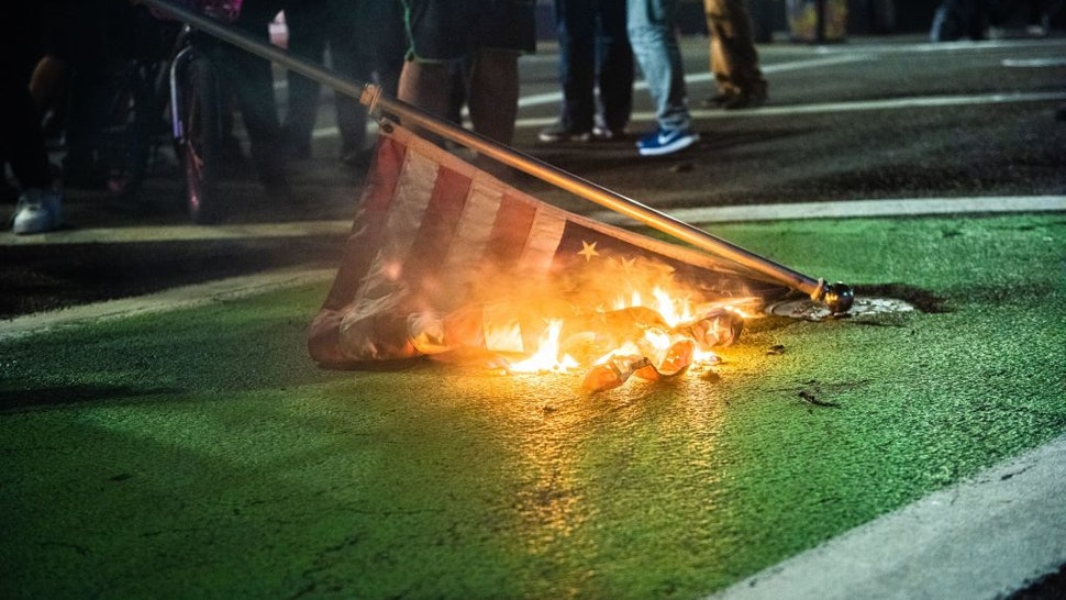 """Protesters burn a US flag in Portland, Oregon on November 4, 2020, during a demonstration called by the """"Black Lives Matter"""" movement, a day after the US Presidential Election"""