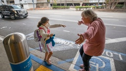LOS ANGELES, CA - NOVEMBER 23: Traveler Jacquie Carney, 7, of San Antonio, TX, runs to hug her grandma, Donna Vidrine, of San Clemente, upon arrival at LAX as the Thanksgiving holiday getaway period gets underway on Monday, Nov. 23, 2020 in Los Angeles, CA. Millions of Americans are carrying on with their travel plans ahead of Thanksgiving weekend despite the CDC's urgent warnings to stay home as the number of daily cases and hospitalizations in the country continue to hit record highs. Confirmed cases in the U.S. for the disease topped 12 million on Saturday as more than 193,000 new infections were recorded in the US on Friday. This broke the previous record for the largest single-day spike on Thursday - and over 82,000 patients are now hospitalized across the country. (Allen J. Schaben / Los Angeles Times via Getty Images)