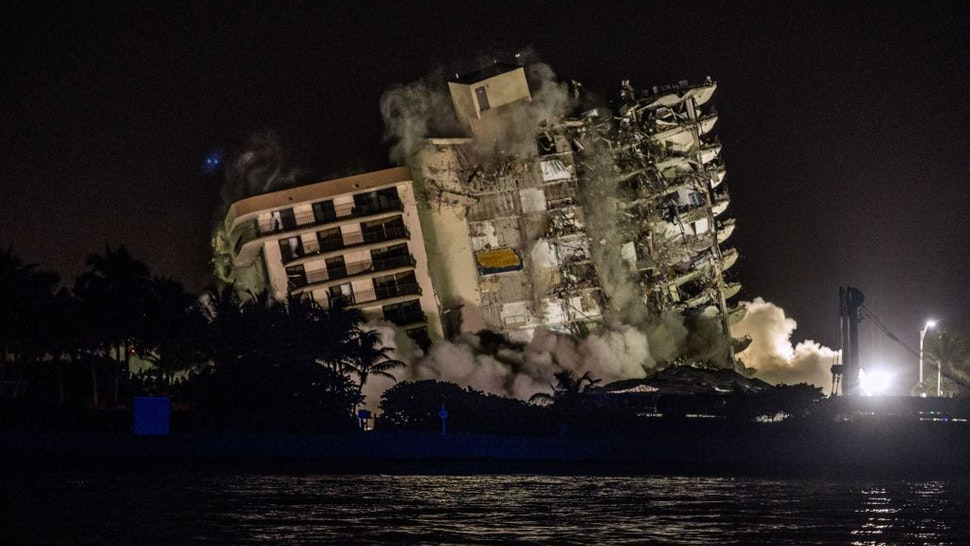 The rest of the Champlain South tower is seen being demolished in Surfside, Florida, north of Miami Beach, late on July 4, 2021. - A controlled explosion brought down the unstable remains of the collapsed apartment block in Florida late on July 4 ahead of a threatening tropical storm as rescuers prepare to resume searching for victims. (Photo by Giorgio VIERA / AFP) (Photo by GIORGIO VIERA/AFP via Getty Images)