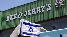 """An Israeli flag is set atop a delivery truck outside US ice-cream maker Ben & Jerry's factory in Be'er Tuvia, on July 21, 2021. - Ben & Jerry's announced that it will stop selling ice cream in the Israel-occupied Palestinian territories since it was """"inconsistent with our values"""", although it said it planned to keep selling its products in Israel. The West Bank and East Jerusalem have been under Israeli control since 1967. Roughly 475,000 Jewish settlers live in the West Bank, in communities widely regarded as illegal under international law, alongside some 2.8 million Palestinians. (Photo by Emmanuel DUNAND / AFP) (Photo by EMMANUEL DUNAND/AFP via Getty Images)"""