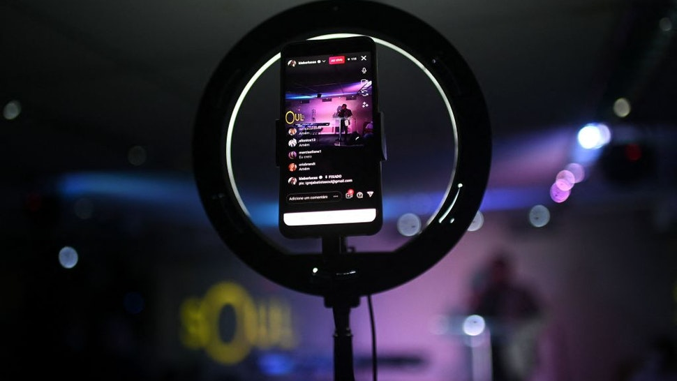 View of a phone through which evangelical pastor and gospel singer Kleber Lucas' service is broadcasted live on his social media at the Soul Church in Rio de Janeiro, Brazil on July 25, 2021. - Brazil's Jair Bolsonaro was elected in 2018 with a strong support of evangelical churches. But support to the far-right president is not unanimous in the sector, with an increasing number of pastors and faithful criticising him openly as Kleber Lucas.
