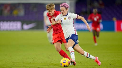 Megan Rapinoe #15 of the United States moves past Quinn #5 of Canada during a game between Canada and USWNT at Exploria Stadium on February 18, 2021 in Orlando City, Florida.