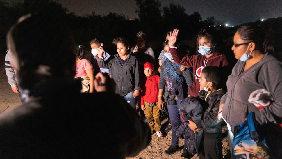 An unaccompanied minor raises her hand after a smuggler rowed her and other immigrants across the Rio Grande at the U.S.-Mexico border on April 9, 2021 in Roma, Texas.