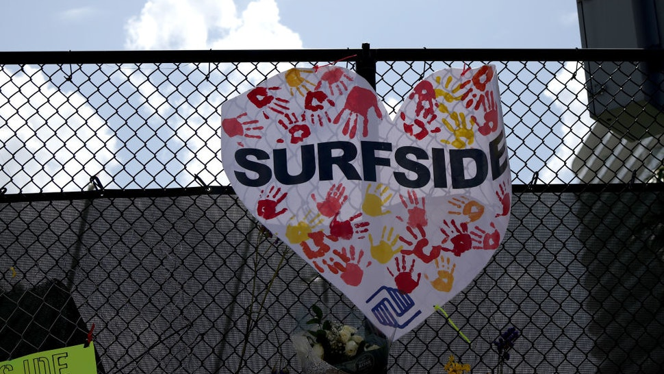 URFSIDE, FLORIDA - JULY 08: Signs are placed near the memorial site for victims of the collapsed 12-story Champlain Towers South condo building on July 08, 2021 in Surfside, Florida. With the death toll currently at 60 and 80 people still missing, rescue workers have shifted the operation to recovery efforts. (Photo by Anna Moneymaker/Getty Images)