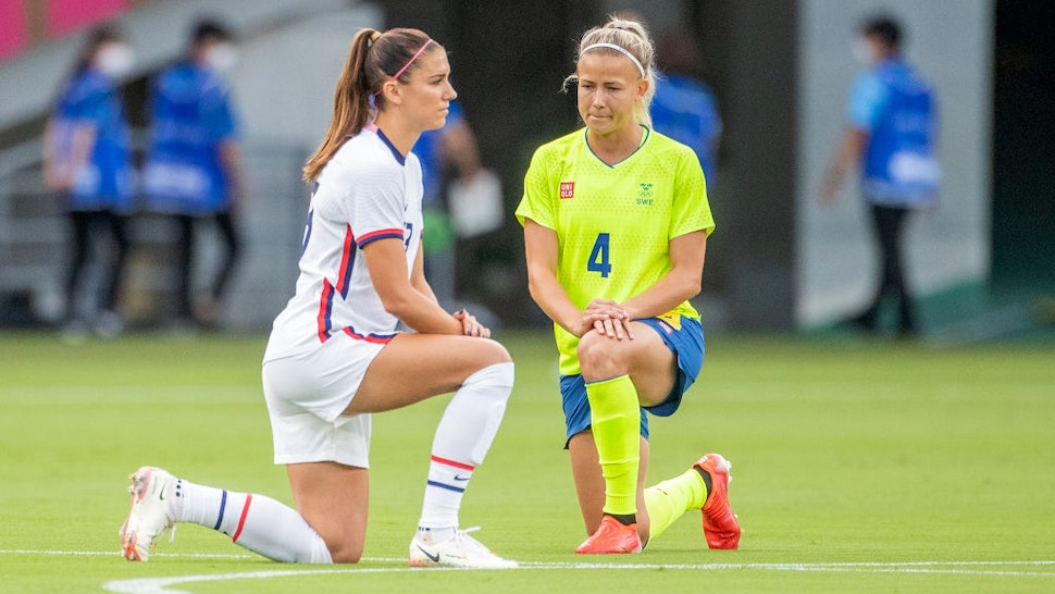 OKYO, JAPAN - JULY 21: Alex Morgan. #13 of the United States and Hanna Glas #4 of Sweden take a knee before the start of the USA V Sweden group G football match at Tokyo Stadium during the Tokyo 2020 Olympic Games on July 21, 2021 in Tokyo, Japan. (Photo by Tim Clayton/Corbis via Getty Images)