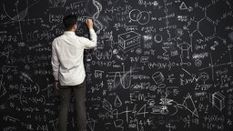 Man writes mathematical equations on chalkboard - stock photo