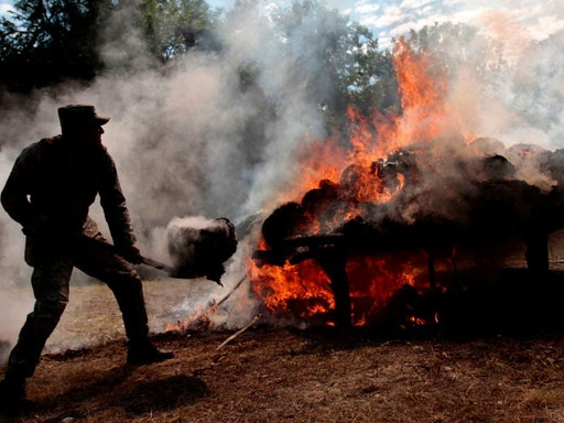 A Mexican Army soldier burns about 945 kilograms of marijuana at the headquarters of IX Militar Region in Acapulco, Guererro state, on December 8, 2011. The drug was seized to alleged members of drugs cartels who operate in the touristic port city of Acapulco. AFP PHOTO/Pedro PARDO (Photo by Pedro PARDO / AFP) (Photo by PEDRO PARDO/AFP via Getty Images)