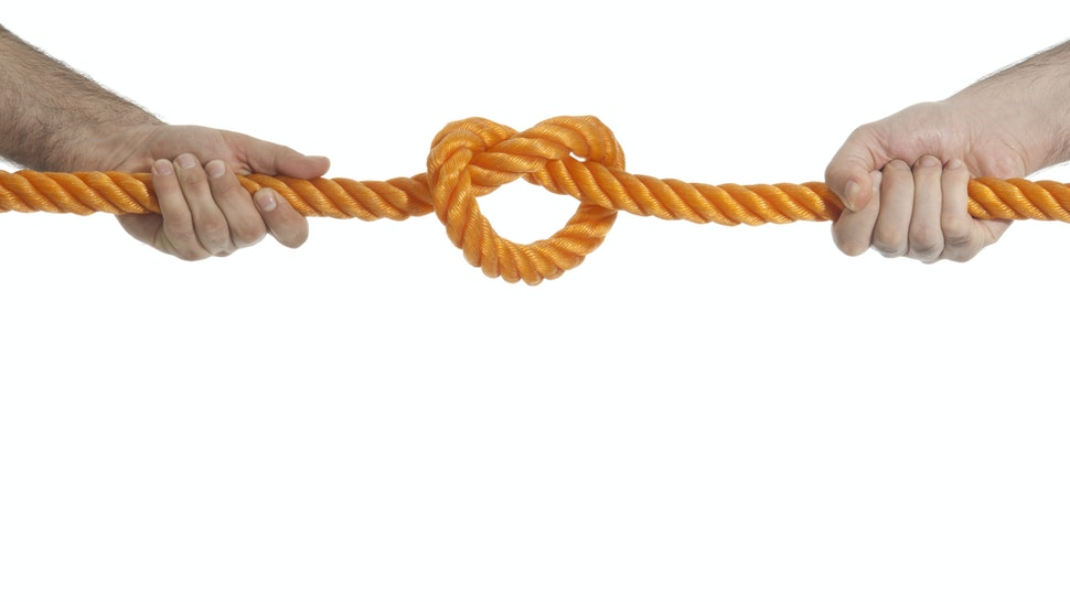 Two hands pulling a rope in opposite direction