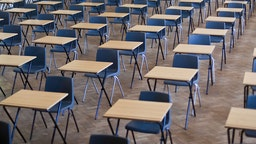 Desks and chairs set out for exams in a school hall in the United Kigdom. (Photo by In Pictures Ltd./Corbis via Getty Images)