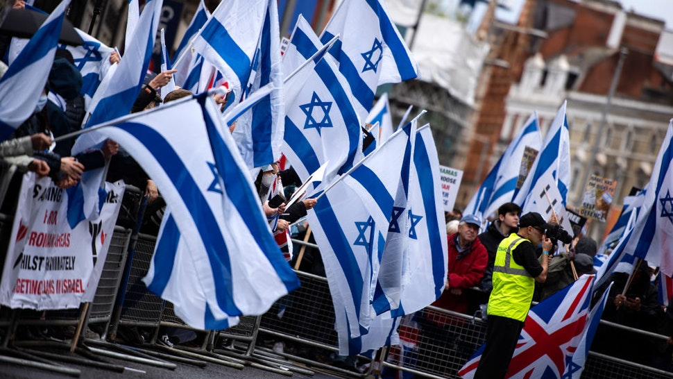 LONDON, UNITED KINGDOM - 2021/05/23: Protesters wave Israeli flags at the Israeli Embassy on High Street Kensington during the demonstration. A pro Israeli demonstration held around Embassy of Israel in solidarity with Israel after cease-fire agreement between Israel and Hamas on May 21, 2021 in Gaza City.