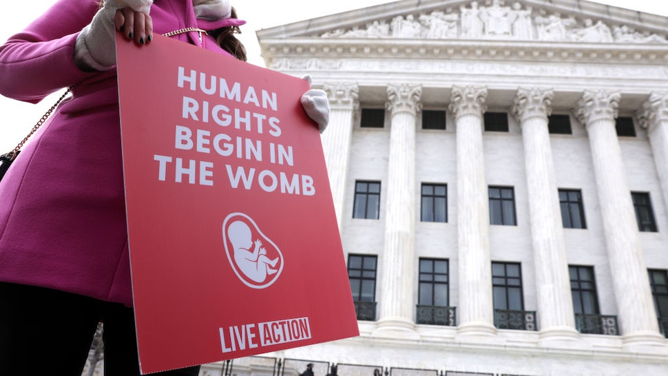 WASHINGTON, DC - JANUARY 29: A pro-life activist holds a sign outside the U.S. Supreme Court during the 48th annual March for Life January 29, 2021 in Washington, DC. Due to the COVID-19 pandemic, a much smaller group of activists participated in the annual march that marked the 1973 Roe v. Wade ruling by the U.S. Supreme Court that had legalized abortion.