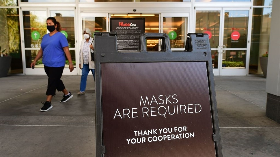 Women wearing facemasks exit a shopping mall where a sign is posted at an entrance reminding people of the mask requirement Westfield Santa Anita shopping mall on June 12, 2020 in Arcadia, California.
