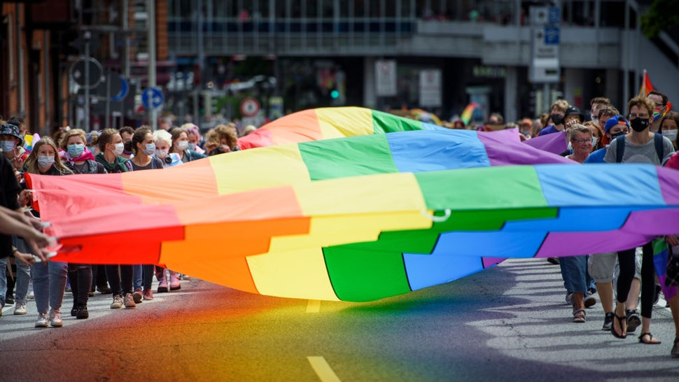 10 July 2021, Schleswig-Holstein, Kiel: Participants carry a huge rainbow flag through the city centre as part of the CSD (Christopher Street Day). The CSD takes place this year only as a demonstration. The traditional street party was cancelled by the organizers due to Corona