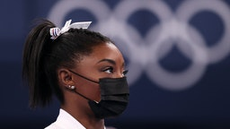 Simone Biles of Team United States watches her team perform on bars after pulling out of the competition after only competing on the vault during the Women's Team Final on day four on day four of the Tokyo 2020 Olympic Games at Ariake Gymnastics Centre on July 27, 2021 in Tokyo, Japan. (Photo by Laurence Griffiths/Getty Images)