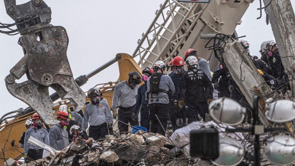 After a brief stop to demolish the standing debris, search and rescue personnel continue to work in the rain on the rubble pile of the 12-story Champlain Towers South condo that partially collapsed on July 5, 2021 in Surfside, Florida. - A controlled explosion brought down the unstable remains of the collapsed apartment block in Florida late on July 4 ahead of a threatening tropical storm as rescuers prepare to resume searching for victims.
