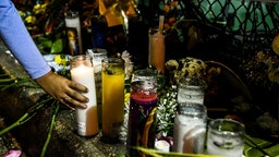 Salome Piedrahita lights a candle at the makeshift memorial for the victims of the building collapse, near the site of the accident in Surfside, Florida, north of Miami Beach on June 30, 2021. - Four more bodies were discovered overnight in the rubble of a collapsed apartment building in Florida, authorities said Wednesday, as the search for more than 140 people unaccounted for entered its seventh day. The official death toll now stands at 16 after most of a building in the Miami-area town of Surfside suddenly pancaked early last Thursday, but hopes are dwindling that the hundreds of rescuers combing the oceanfront site will find anyone alive.