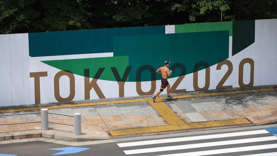 ARIAKE, TOKYO, JAPAN - 2021/06/28: A jogger runs in Odaiba Marine Park in Ariake, Tokyo. 25 Days before the opening ceremony of the Tokyo 2020 Summer Olympic Games many sporting venues and fan zones are still under construction.
