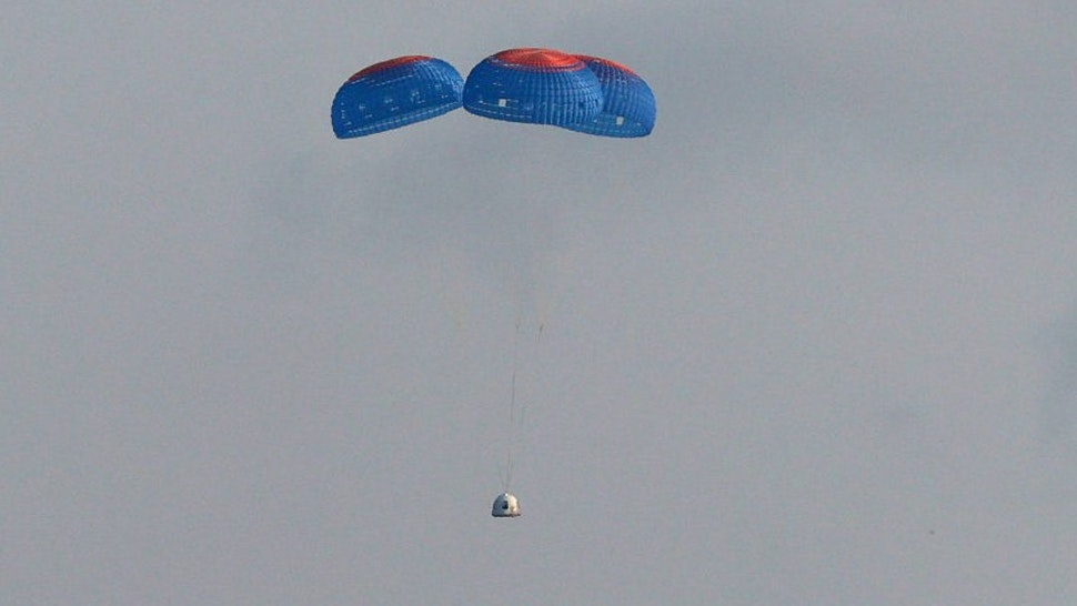 VAN HORN, TEXAS - JULY 20: Blue Origin's New Shepard crew capsule descends on the end of its parachute system carrying Jeff Bezos along with his brother Mark Bezos, 18-year-old Oliver Daemen, and 82-year-old Wally Funk on July 20, 2021 in Van Horn, Texas. Mr. Bezos and the crew are riding in the first human spaceflight for the company. (Photo by