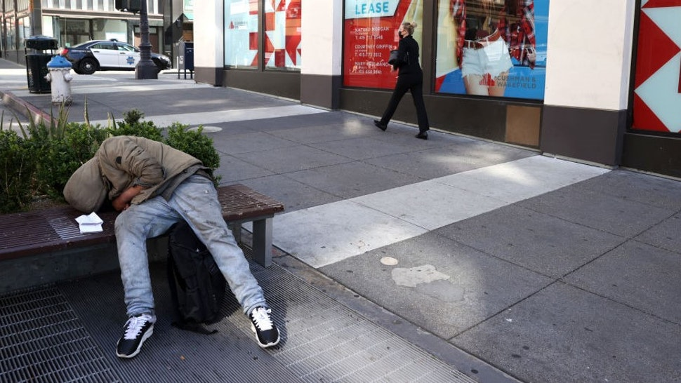 SAN FRANCISCO, CALIFORNIA - APRIL 16: A homeless person sleeps on a bench in front of closed retail stores on April 16, 2021 in San Francisco, California. As San Francisco begins to slowly reopen a year after the city went into lockdown due to theCOVID-19 pandemic, many of the city's businesses have shut their doors forever. San Francisco mayor London Breed is asking San Franciscans to patronize local businesses for the next 30 days as she pushes to prioritize small businesses. (Photo by