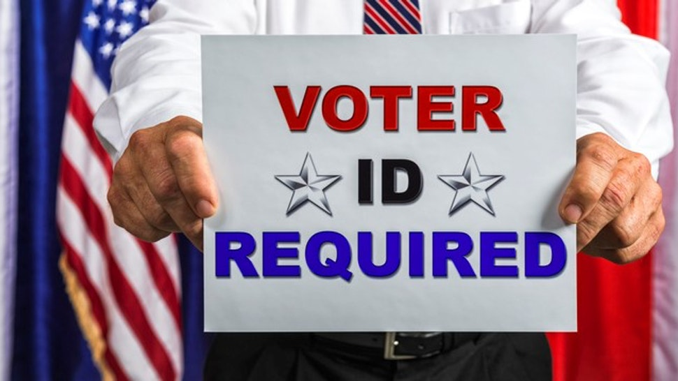 Businessman holding a sign that reads Voter ID Required