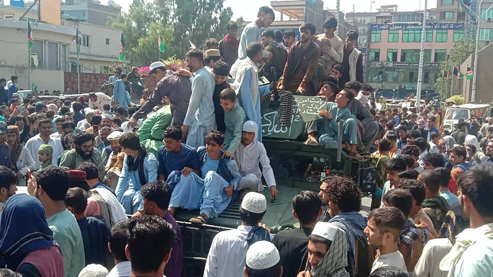 TOPSHOT - Taliban fighters and local people sit on an Afghan National Army (ANA) Humvee vehicle on a street in Jalalabad province on August 15, 2021.