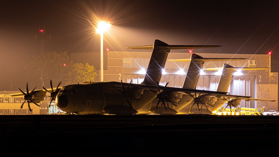 15 August 2021, Lower Saxony, Wunstorf: Airbus A400M transport aircraft of the German Air Force stand behind a fence at the Wunstorf air base in the Hanover region in the evening. In view of the rapid advance of the Taliban in Afghanistan, the Bundeswehr plans to begin evacuating German citizens and local Afghan forces from Kabul on Monday (16.08.2021).