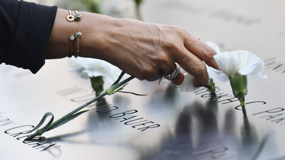 US-ATTACKS-9/11-ANNIVERSARY A mourner places flowers at the 9/11 Memorial & Museum in New York on September 11, 2020, as the US commemorates the 19th anniversary of the 9/11 attacks. (Photo by Angela Weiss / AFP) (Photo by ANGELA WEISS/AFP via Getty Images) ANGELA WEISS / Contributor via Getty Images