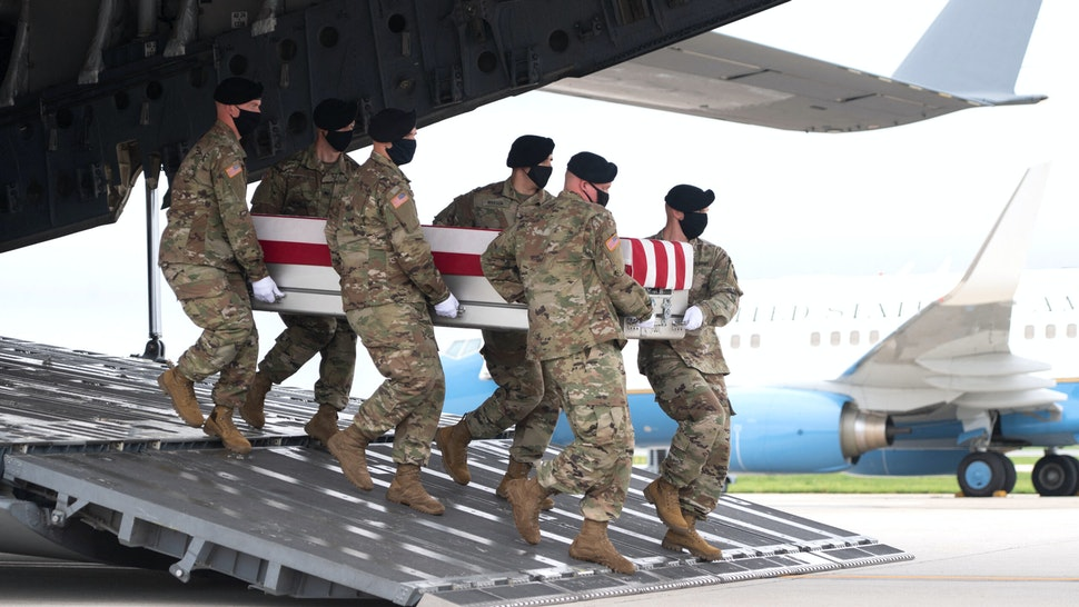 A transfer case with the remains of Army Staff Sgt. Ryan C. Knauss, 23, of Corryton, Tennessee, are carried off of a military aircraft as US President Joe Biden attends the dignified transfer at Dover Air Force Base in Dover, Delaware, August, 29, 2021, one of the 13 members of the US military killed in Afghanistan last week. - President Joe Biden prepared Sunday at a US military base to receive the remains of the 13 American service members killed in an attack in Kabul, a solemn ritual that comes amid fierce criticism of his handling of the Afghanistan crisis. Biden and his wife, Jill, both wearing black and with black face masks, first met far from the cameras with relatives of the dead in a special family center at Dover Air Force Base in Delaware.The base, on the US East Coast about two hours from Washington, is synonymous with the painful return of service members who have fallen in combat.
