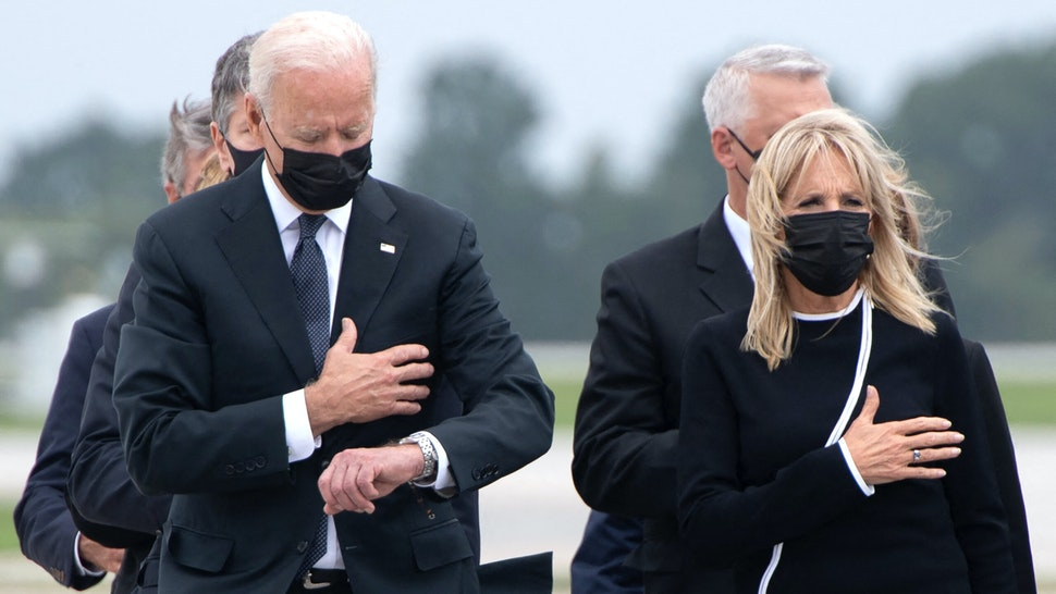 US President Joe Biden looks down alongside First Lady Jill Biden as they attend the dignified transfer of the remains of a fallen service member at Dover Air Force Base in Dover, Delaware, August, 29, 2021, one of the 13 members of the US military killed in Afghanistan last week. - President Joe Biden prepared Sunday at a US military base to receive the remains of the 13 American service members killed in an attack in Kabul, a solemn ritual that comes amid fierce criticism of his handling of the Afghanistan crisis. Biden and his wife, Jill, both wearing black and with black face masks, first met far from the cameras with relatives of the dead in a special family center at Dover Air Force Base in Delaware.The base, on the US East Coast about two hours from Washington, is synonymous with the painful return of service members who have fallen in combat.