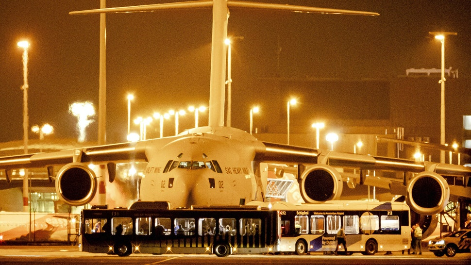Passengers from Afghanistan disembark from a C-17 plane used by several NATO countries, at a platform at Schiphol airport near Amsterdam, on August 18, 2021.