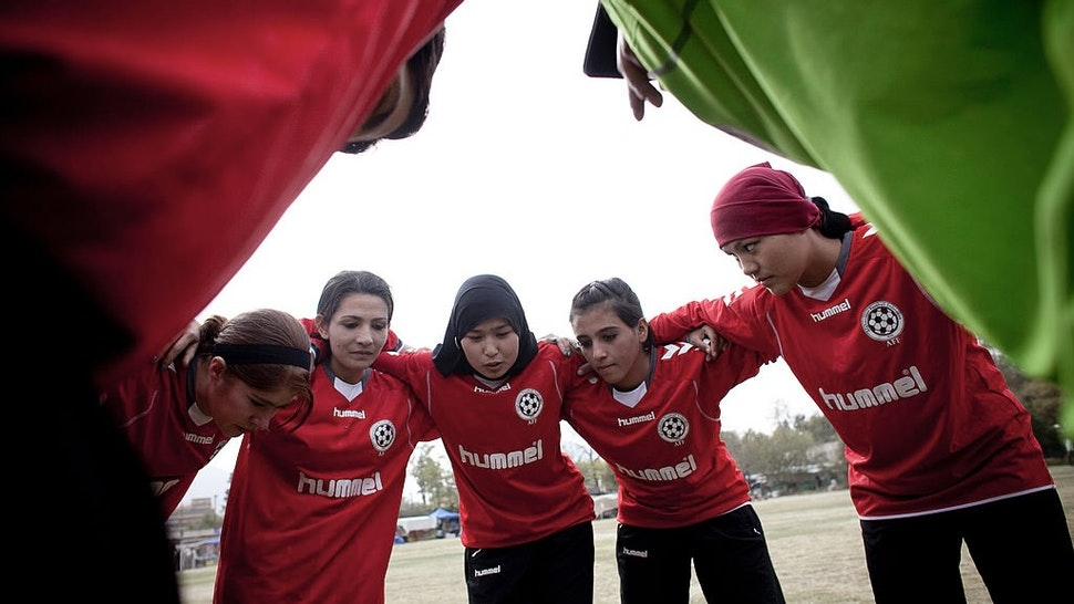 Afghan Women's National Football Team Play A Match Against The ISAF AFGHANISTAN, KABUL - OCTOBER 29: Members of the Afghan women's national football team huddles during a match with the NATO-led International Security Assistance Force (ISAF) women's team in a friendly football match at the ISAF headquarters in Kabul on October 29, 2010 in Kabul, Afghanistan. The Afghan women's team won 1-0. (Photo by Majid Saeedi/Getty Images) Majid Saeedi / Stringer via Getty Images